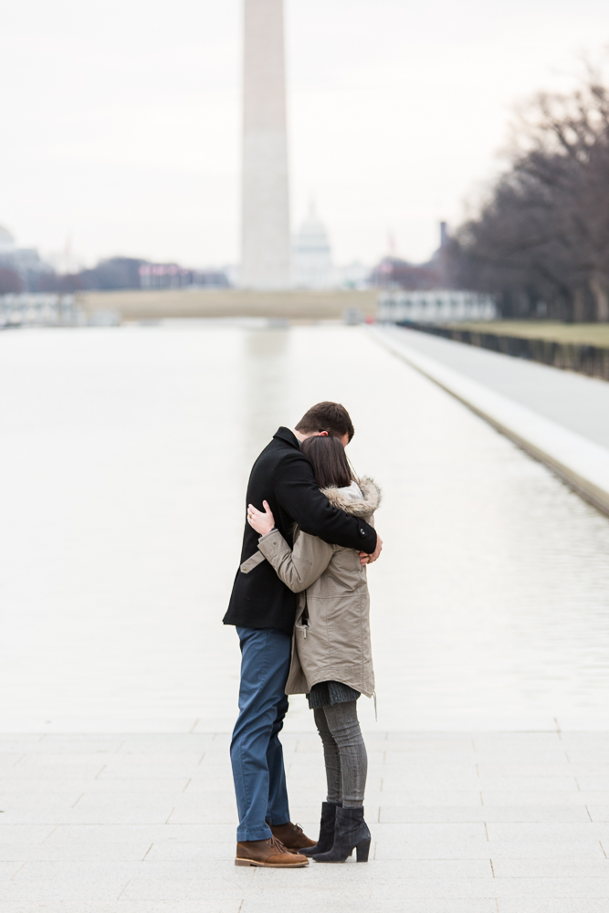 Newly engaged couple hugs after the proposal at the monuments