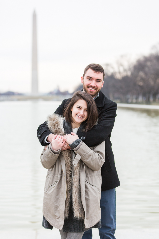 Smiling couple right after their engagement in front of the Reflecting Pool and Washington Monument   Washington DC proposal photography
