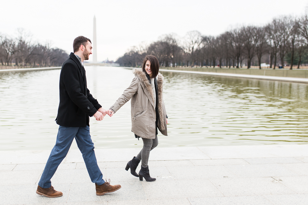 Engaged couple walking along the Reflecting Pool while holding hands