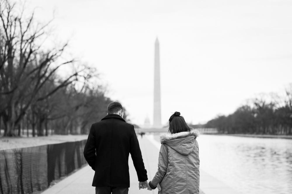 Black and white engagement photo, walking along the Reflecting Pool towards the Washington Monument | National Mall engagement pictures
