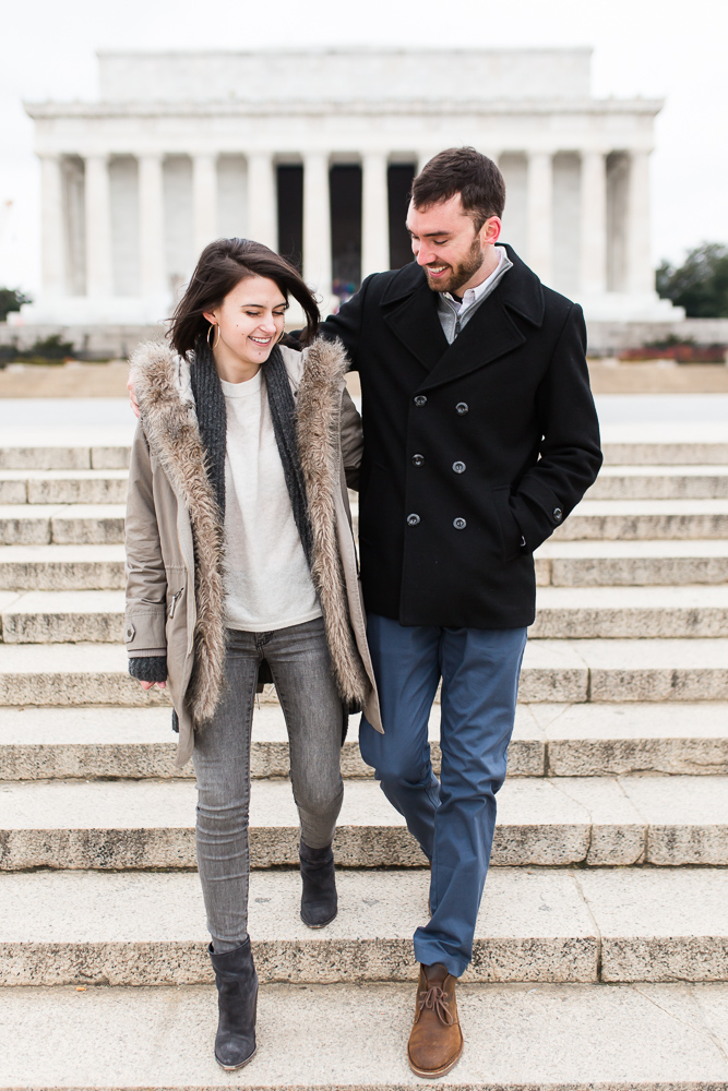 Engaged couple walking down the steps in front of the Lincoln Memorial with arms around each other
