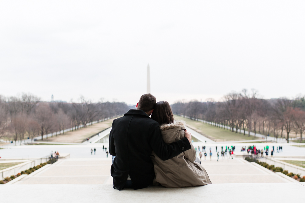 Newly engaged couple sitting on the steps of the Lincoln while looking out at the Reflecting Pool and Lincoln Memorial during their winter engagement shoot