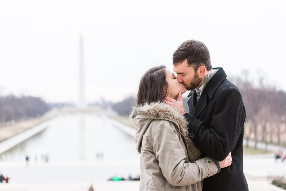 Couple kissing during a DC winter engagement shoot with Reflecting Pool and Washington Monument in the background