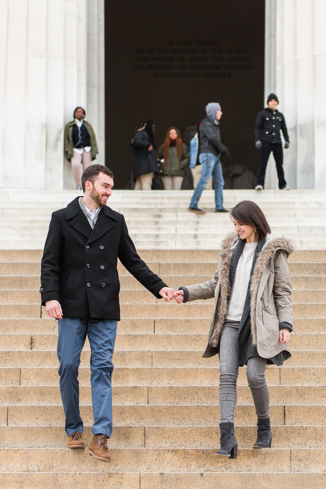 Holding hands as they walk down the steps of the Lincoln Memorial during a winter engagement session
