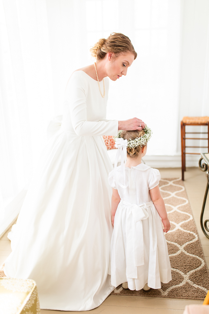 Bride helping the flower girl put on her floral crown