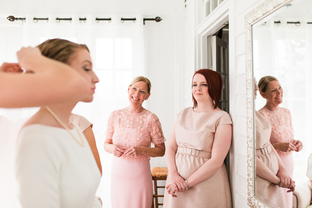 Mother-of-the-bride and bridesmaid smiling as they watch the bride get ready | Candid Northern Virgina wedding photographer