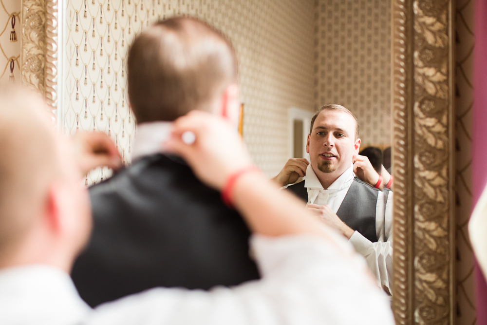 Groom looking in mirror of the Gilded Fox Ballroom as he gets ready
