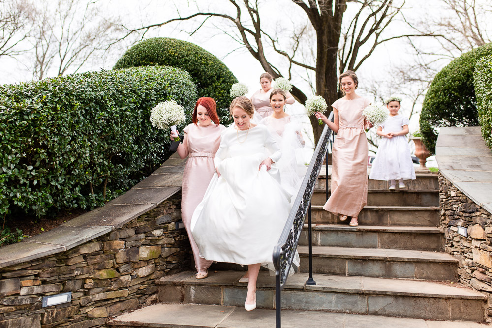 Bride and bridesmaids walking down the steps onto the patio at Black Horse Inn