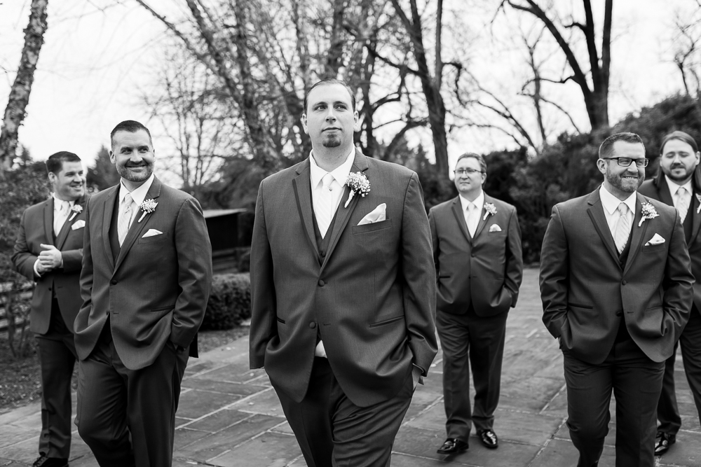 Groom walking across the patio with his groomsmen