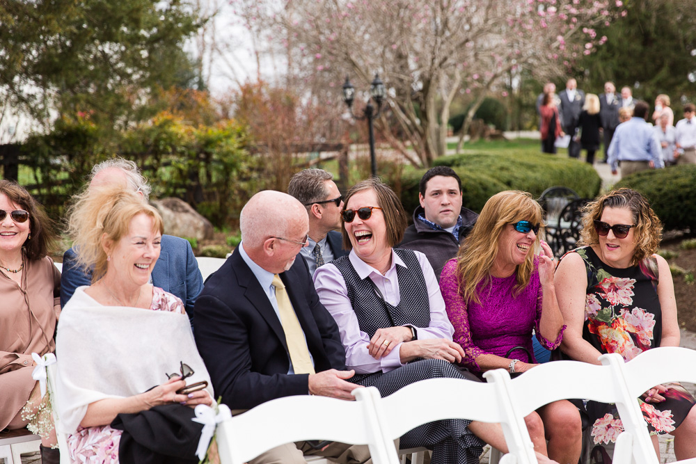 Candid picture of wedding guests laughing before the outdoor ceremony at Black Horse Inn
