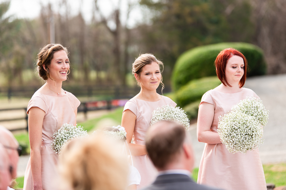 Bridesmaids in light pink dresses smile during the wedding ceremony