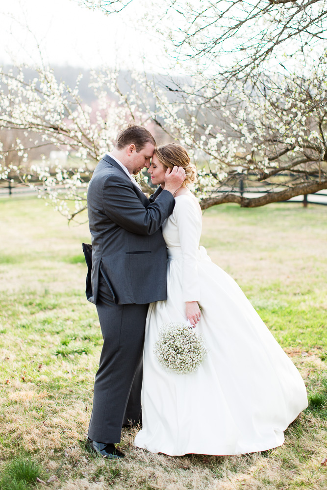 Sweet photo of bride and groom by a cherry blossom tree