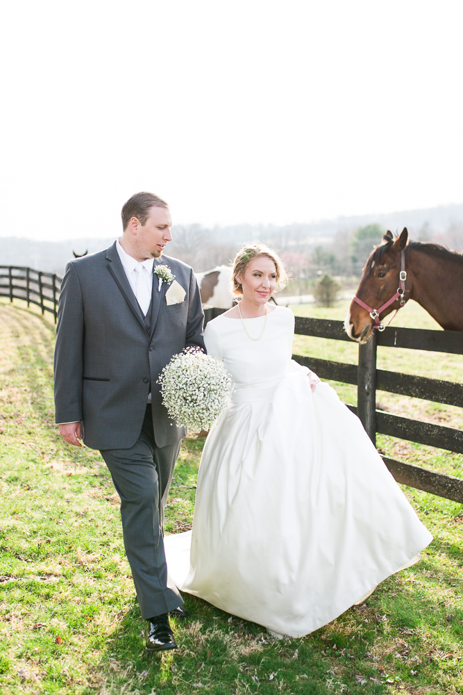 Bride and groom walk along the fence with horses at Black Horse Inn