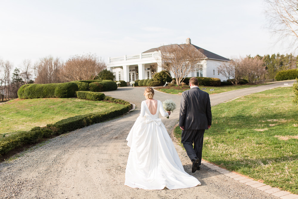 Husband and wife walking along the road to their wedding reception at the Gilded Fox Ballroom