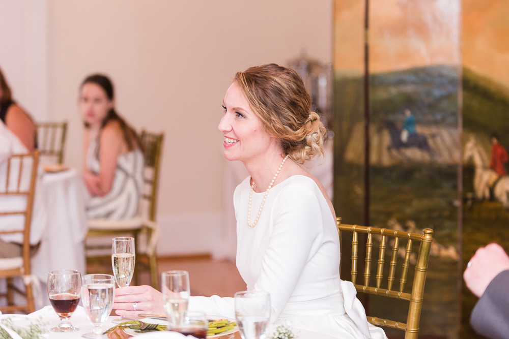 Candid photo of bride smiling as she listens to the toasts during her wedding reception