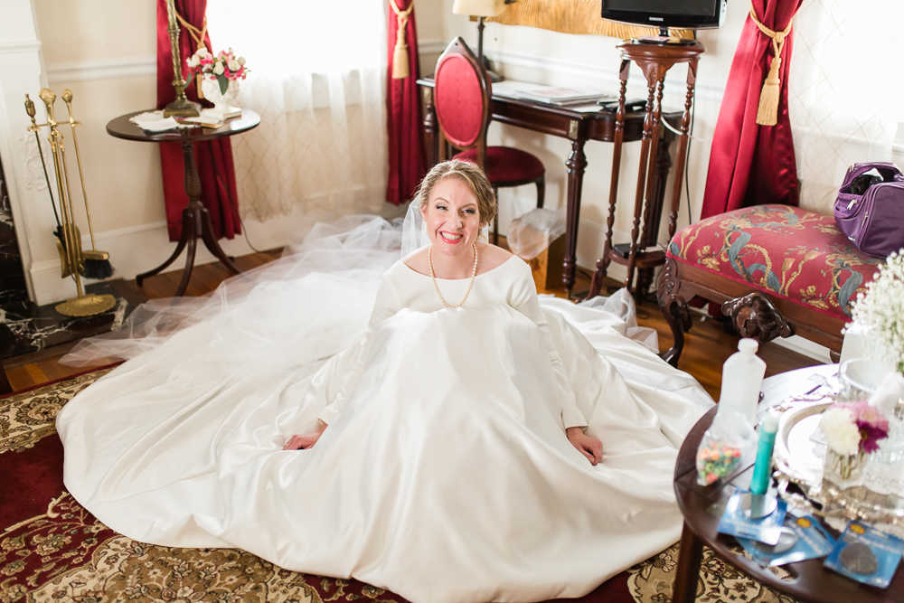 Bride sitting on the floor of the bridal suite as she rests before the wedding ceremony | Black Horse Inn, Warrenton, Virginia