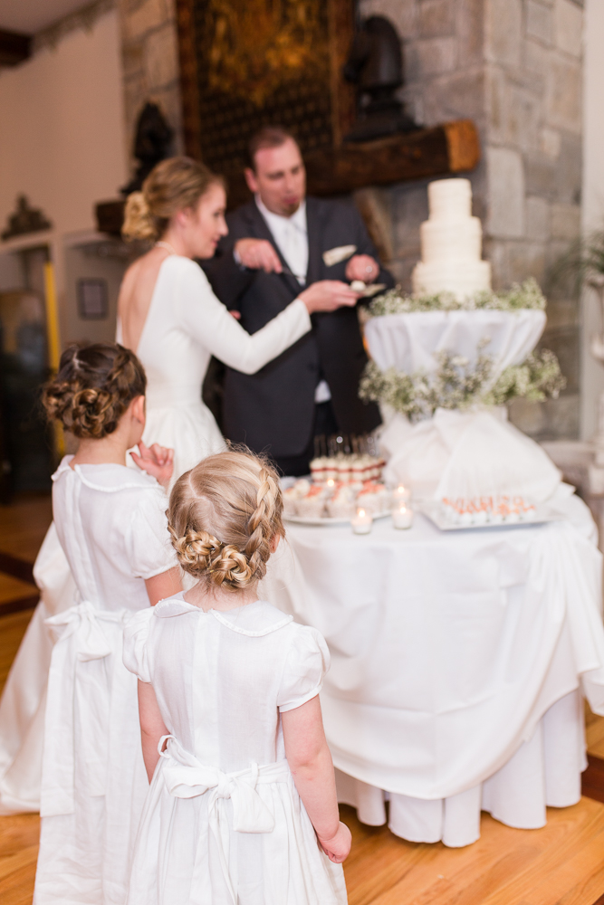 Flower girls watch as bride and groom cut their wedding cake