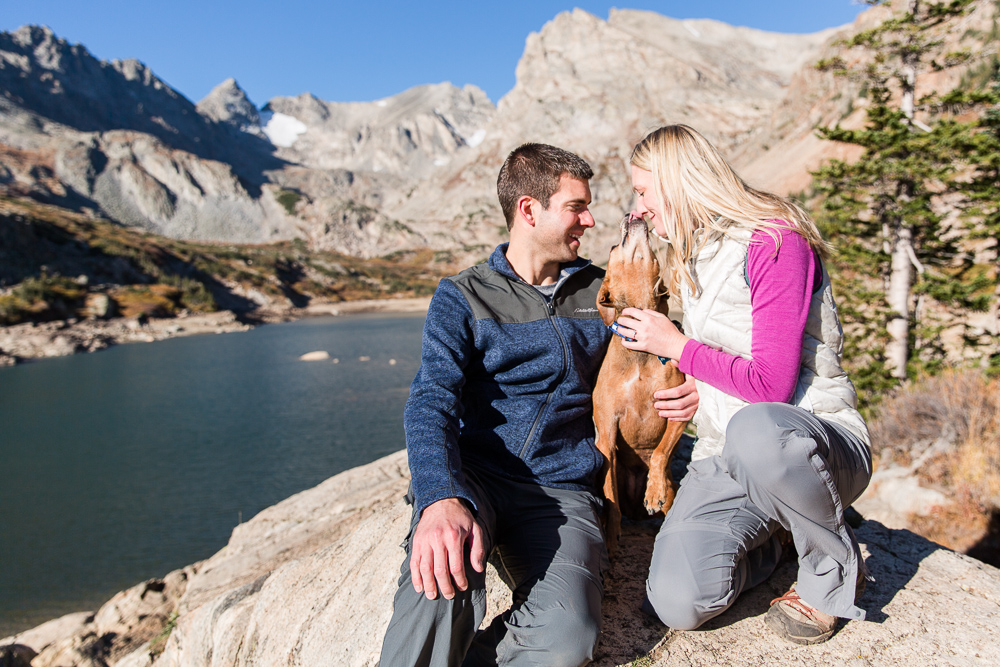 Dog giving kisses during an engagement shoot in the mountains