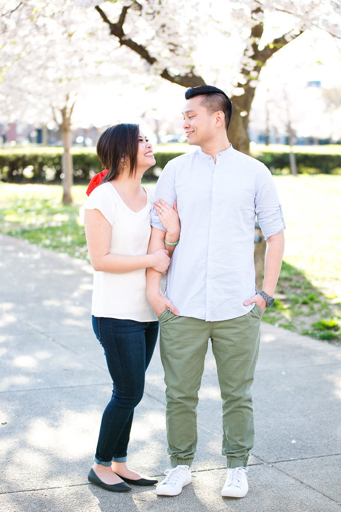 Happy engaged couple during their cherry blossom engagement in DC
