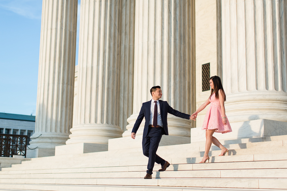 Engaged couple holding hands as they walk down the Supreme Court steps | Engagement photo outfit ideas - blush pink dress and navy suit