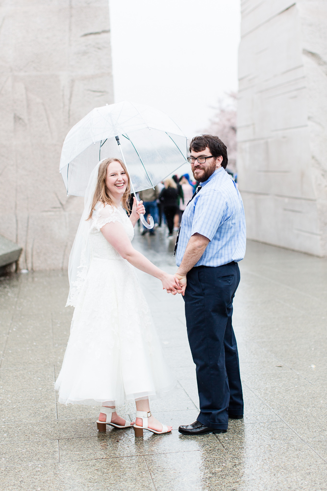 Rainy wedding pictures as bride and groom walk around the DC monuments