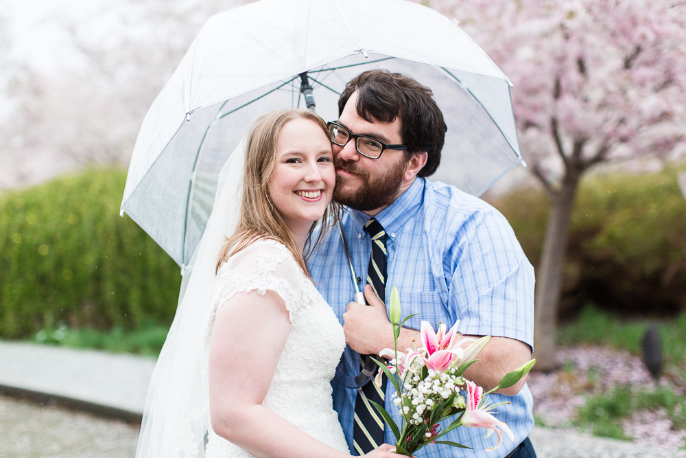 Wedding couple cuddles under an umbrella on their rainy DC wedding day