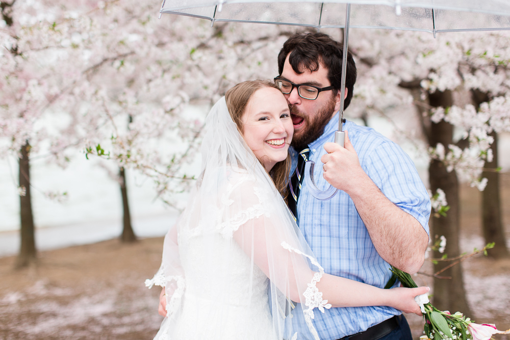 Wedding couple having fun as they pose under the cherry blossom trees