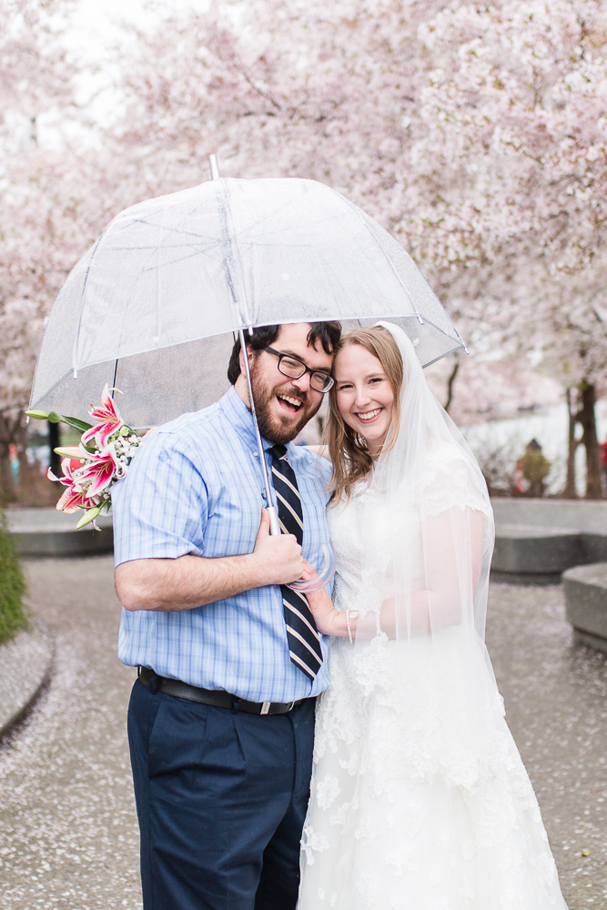 Smiling bride and groom under an umbrella, surrounded by cherry blossom trees at the Tidal Basin in Washington, DC