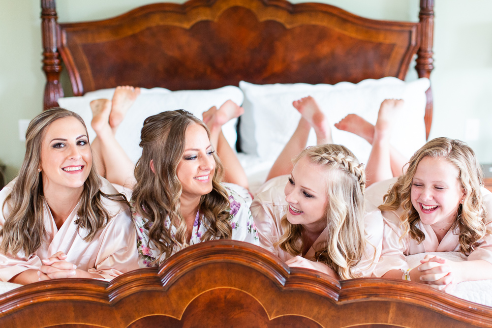 Candid photo of bride and her sisters on the bed at The Aventador house at Mount Ida Farm