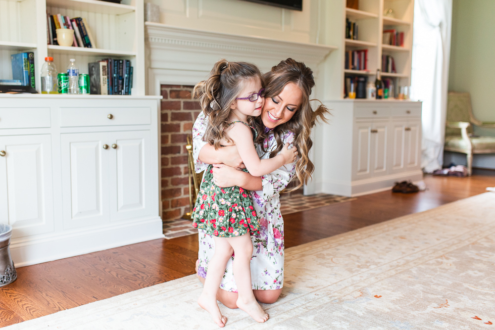 Bride hugging her niece while getting ready for the wedding day