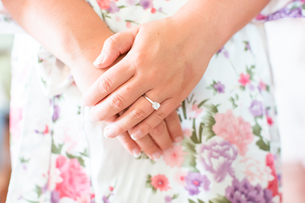 Close up photo of bride's hands and engagement ring against her floral robe