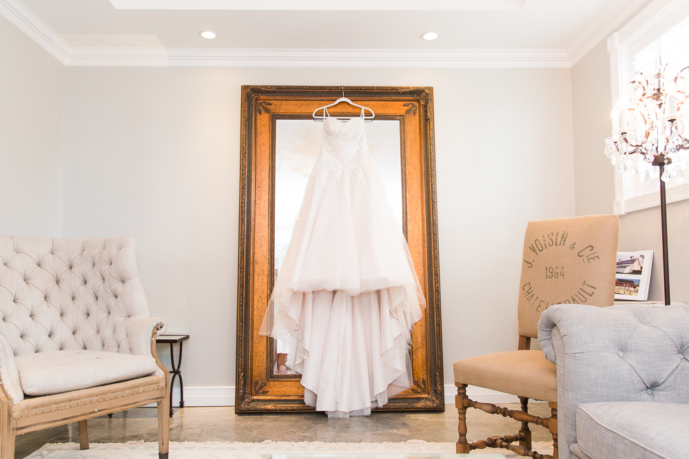 Ava Laurenne wedding dress hanging from the mirror in the Lodge at Mount Ida Farm bridal suite in Charlottesville, Virginia