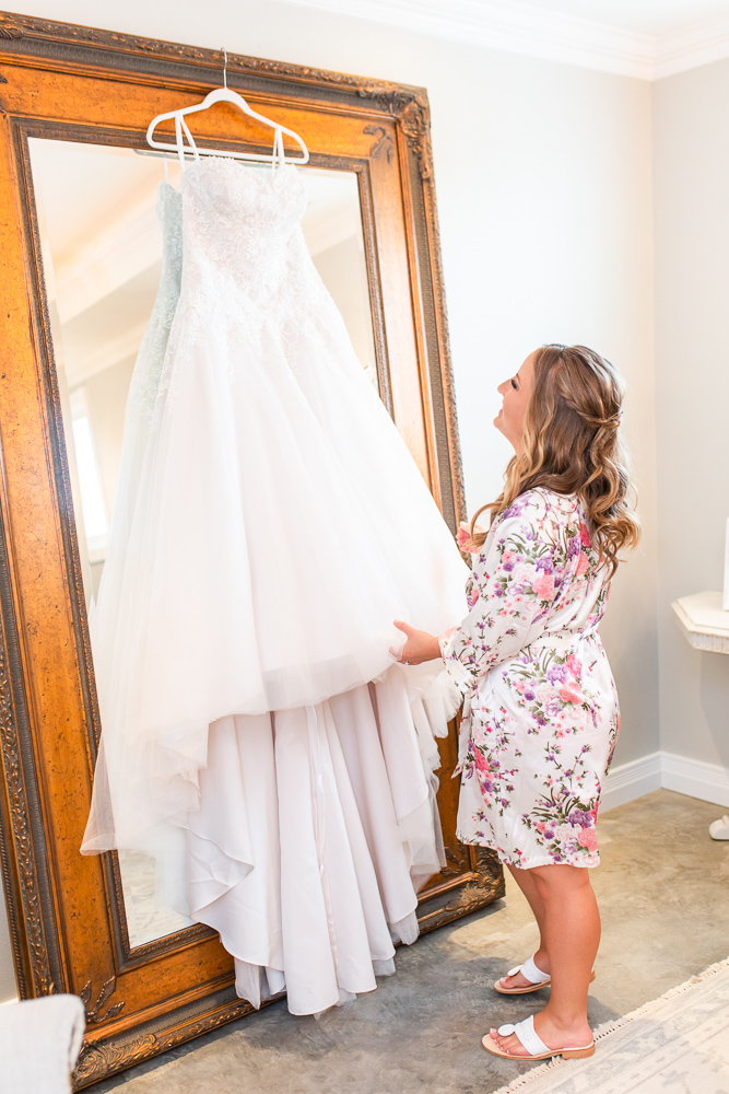 Bride looking up at her wedding dress as it hangs in the bridal suite at Mount Ida Farm