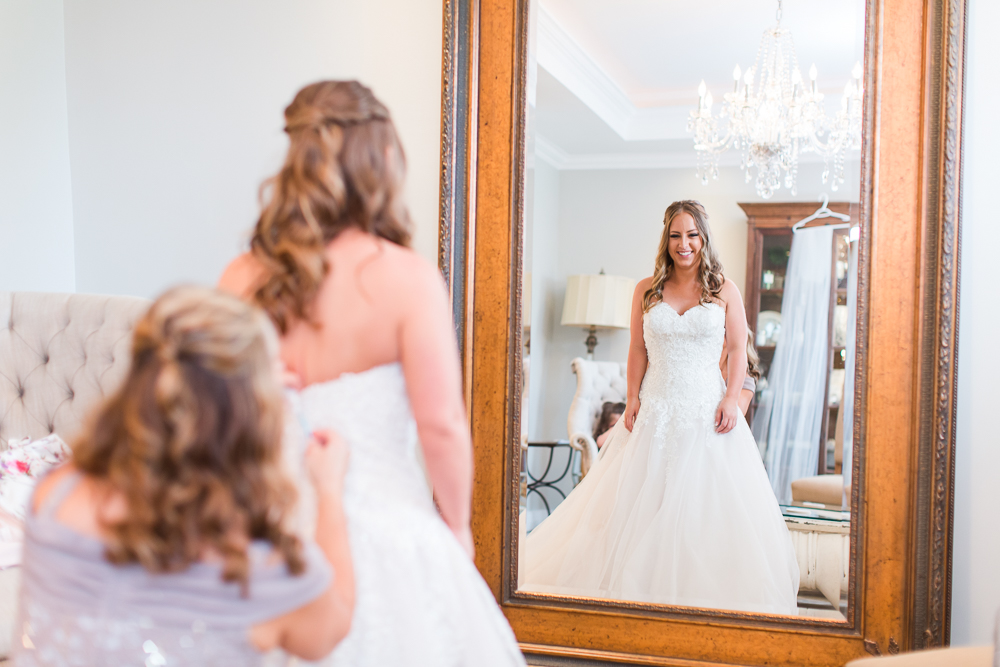 Bride looking in the mirror as her mom helps tie up her wedding dress in the Lodge at Mount Ida Farm in Charlottesville, Virginia