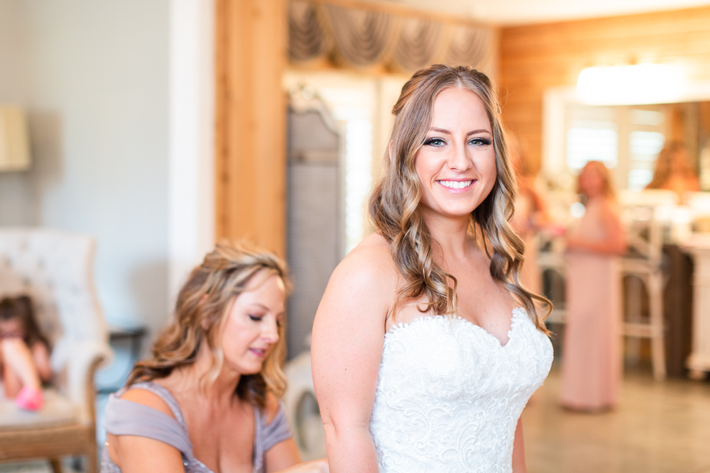 Smiling at the camera as mom buttons up the wedding dress in Charlottesville, Virginia