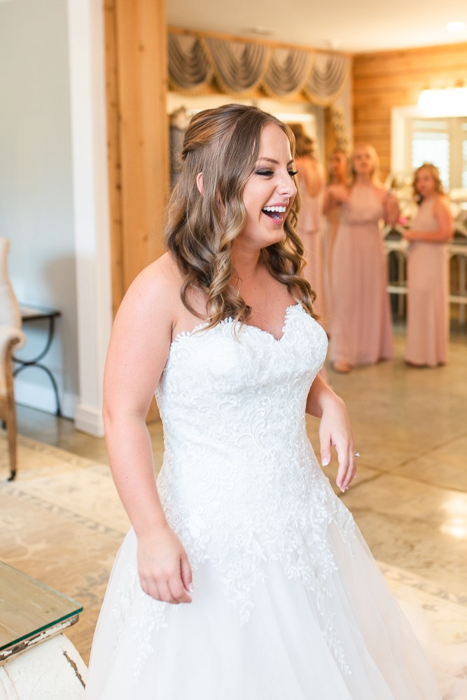 Candid moment of laughter as bride puts on her dress