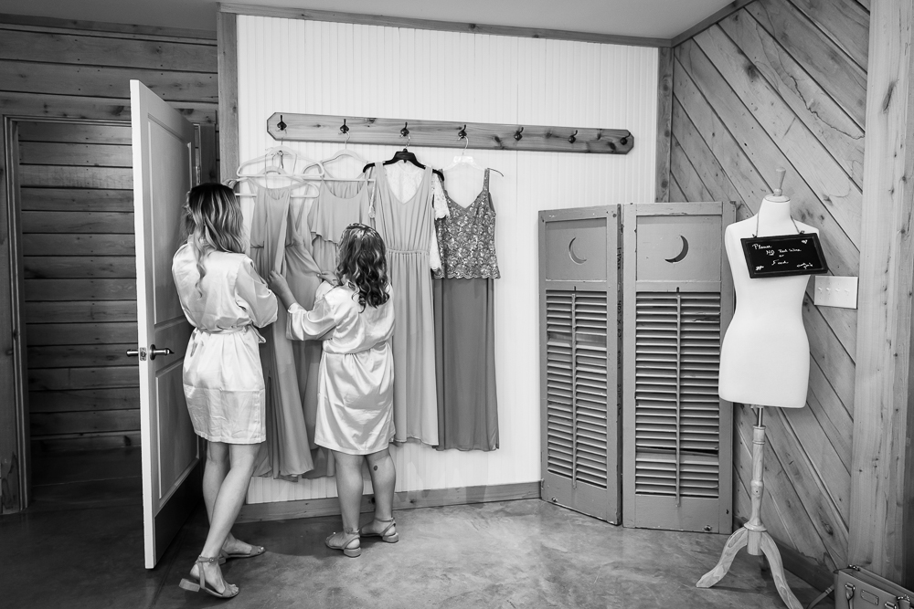 Bridesmaids looking at their dresses as they hang in the bridal suite at The Lodge at Mount Ida Farm