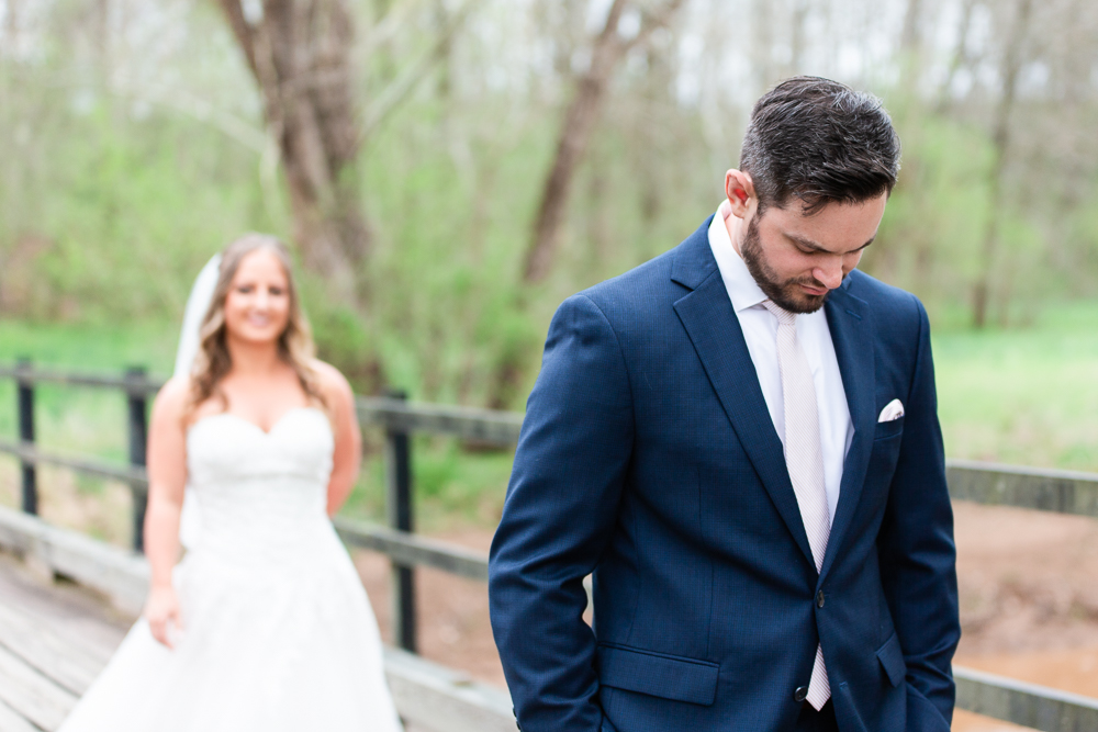 Bride walking up to the groom for their First Look on a bridge in Charlottesville, VA
