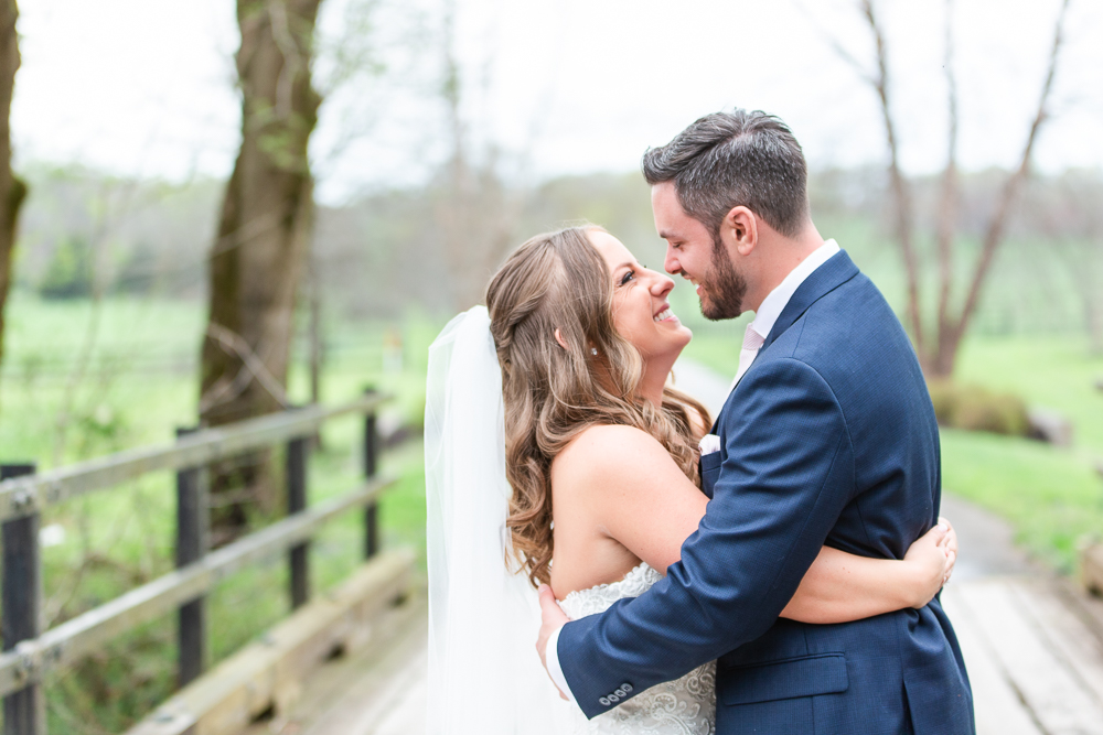 Bride and groom hug and look into each other's eyes while standing on the bridge at Mount Ida