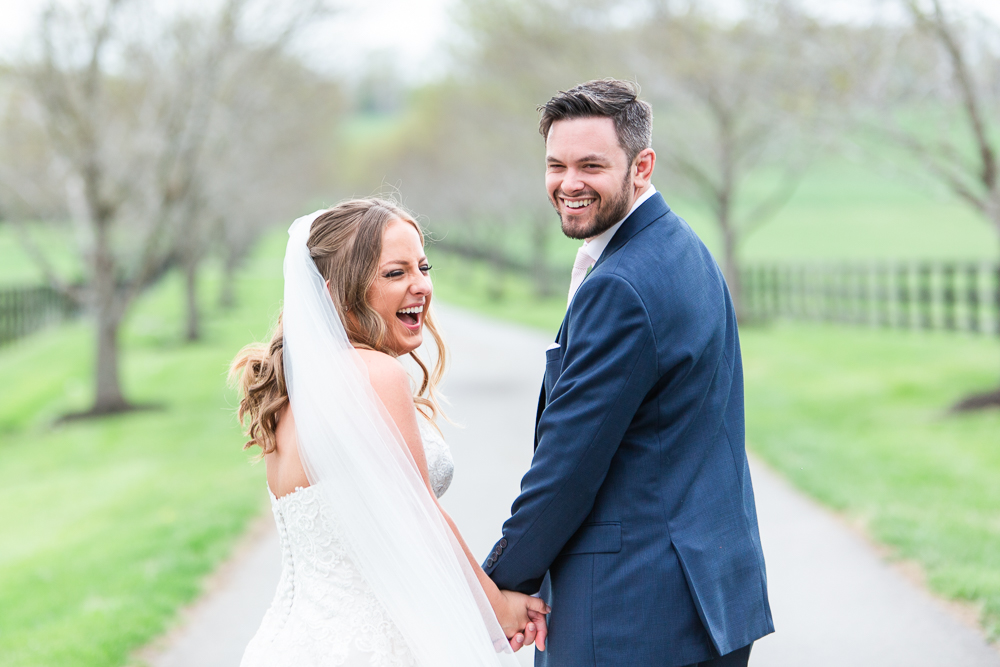 Bridge laughing as she holds hands with the groom at Mount Ida Farm | Fun Charlottesville wedding photographer
