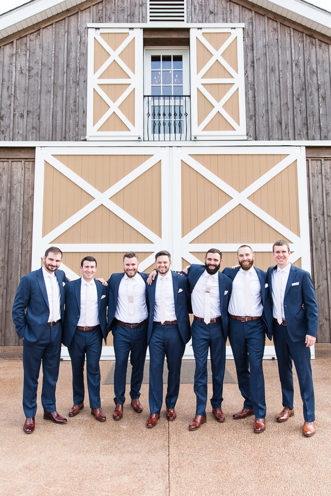 Groomsmen standing with their arms around each other in front of the big barn doors at The Lodge at Mount Ida Farm