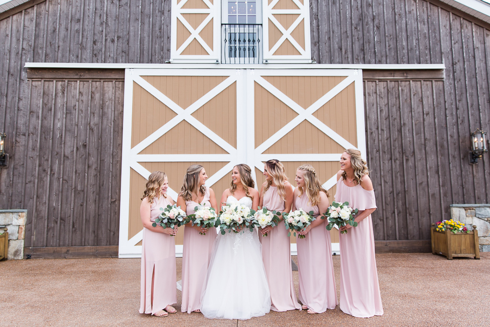 Bride with her bridesmaids in long, blush dresses, standing in front of the Lodge at Mount Ida Farm in Charlottesville