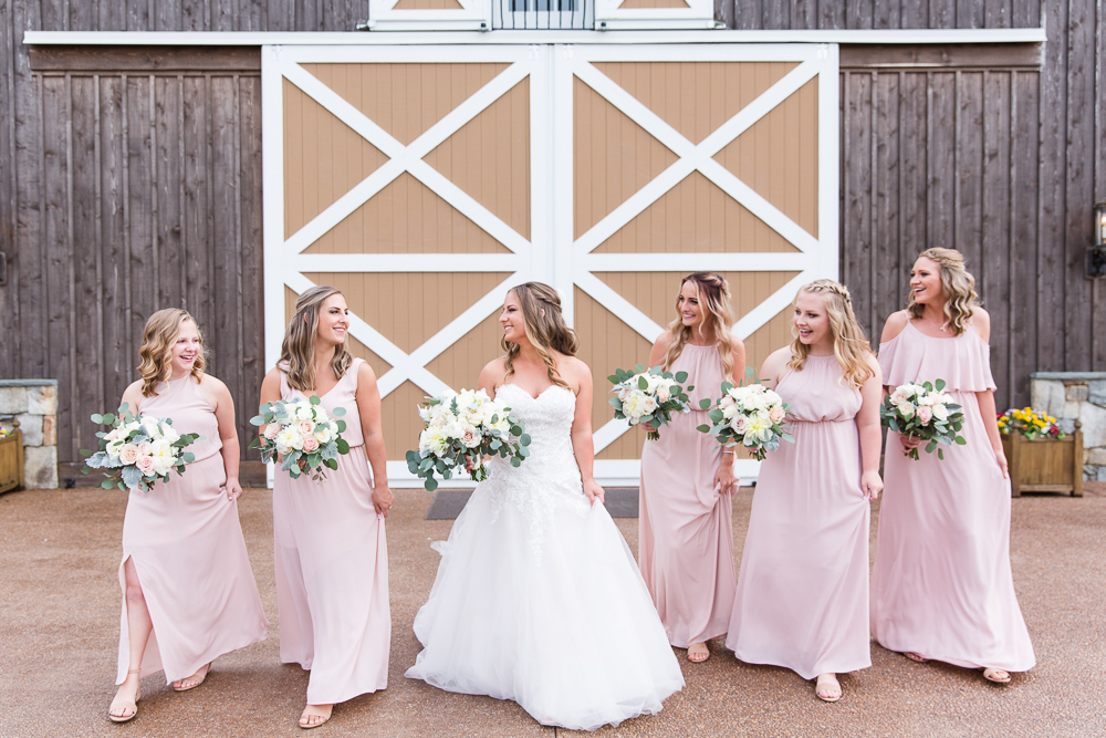 Bride smiling at her bridesmaids as they walk in front of the barn at The Lodge at Mount Ida Farm