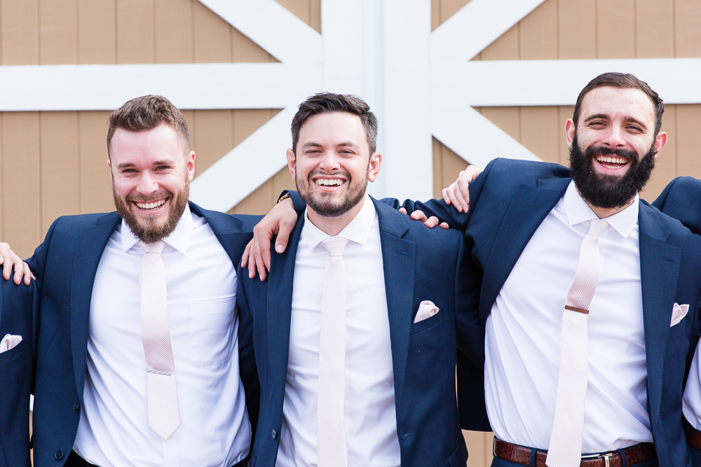Groom laughing with his groomsmen on the wedding day