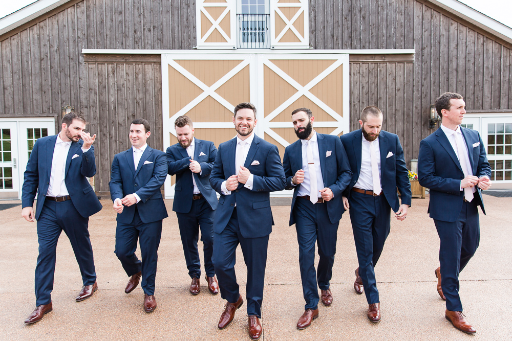 Groomsmen in navy suits, walking away from the barn doors at The Lodge at Mount Ida Farm | Charlottesville, Virginia wedding