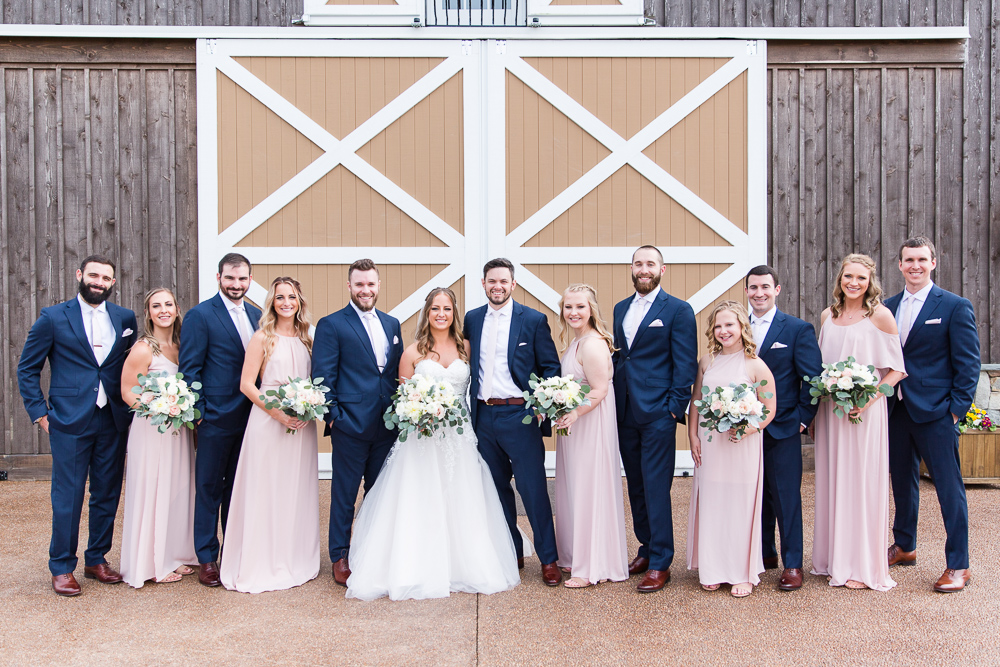 Full bridal party, wearing navy and blush, posing for wedding pictures in front of The Lodge at Mount Ida Farm in Charlottesville