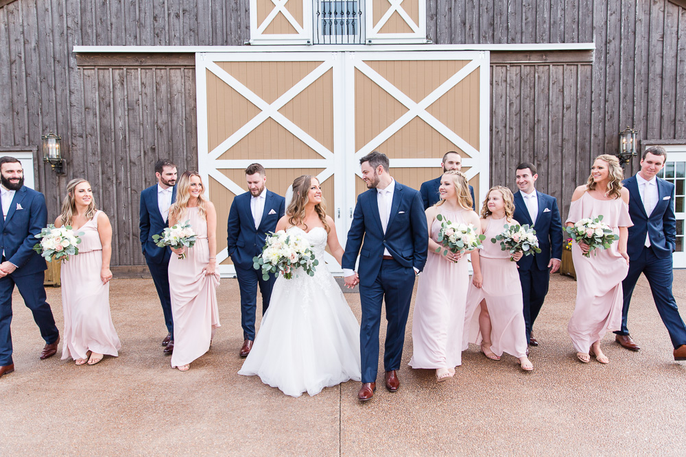 Wedding party in blush and navy in front of the barn doors at The Lodge at Mount Ida Farm