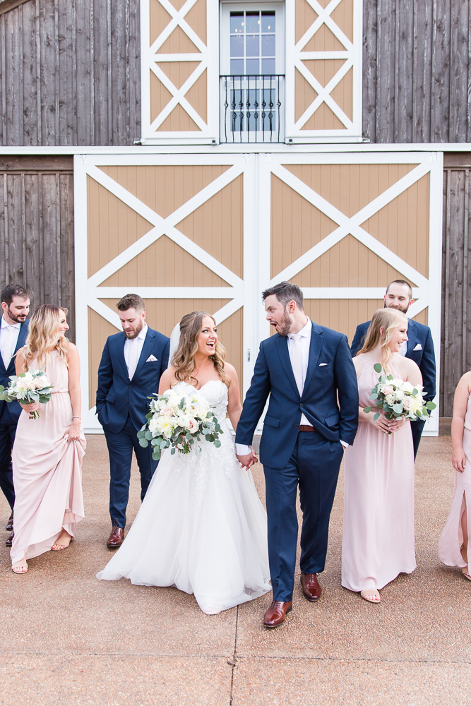Candid picture of wedding couple walking with the bridal party in Charlottesville, VA