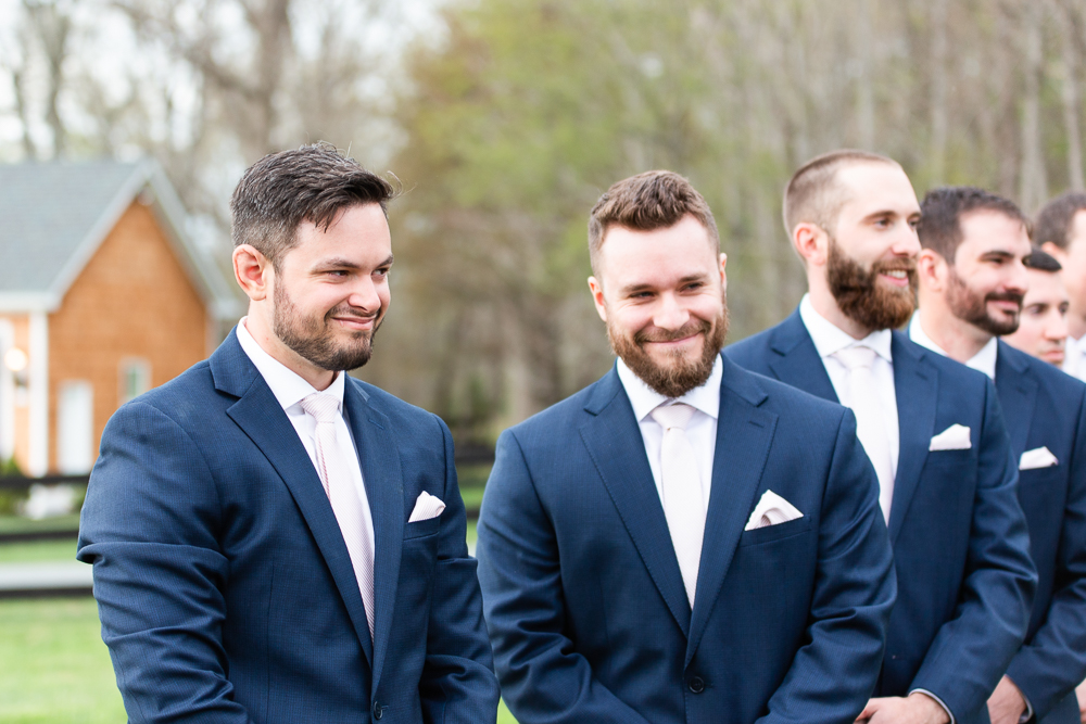 Groom smiling as he watches bride walk down the aisle