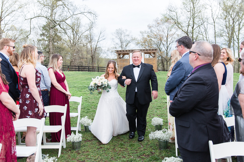 Bride walking down the aisle with her father at her Mount Ida wedding ceremony